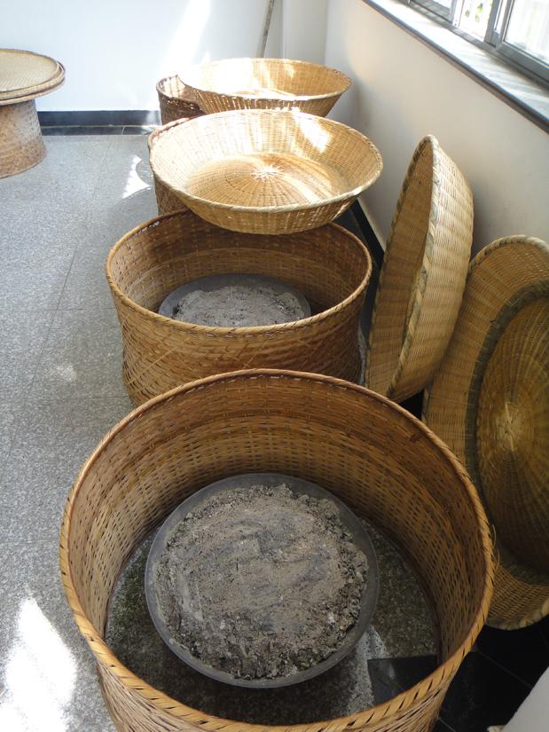 Bastkörbe mit von Asche bedeckter Holzkohle zum Rösten von Grüntee