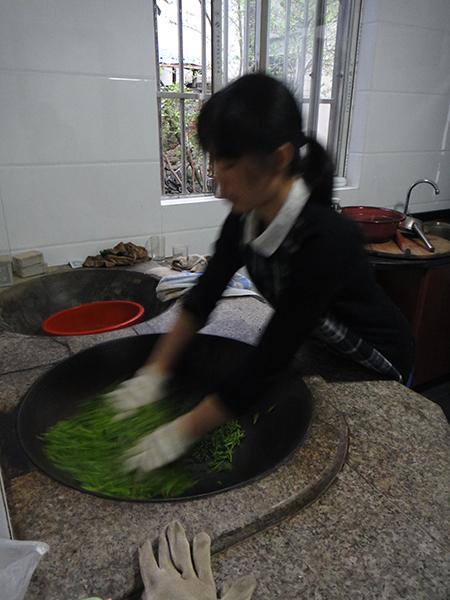 Die frischen Blätter werden im Wok befeuert